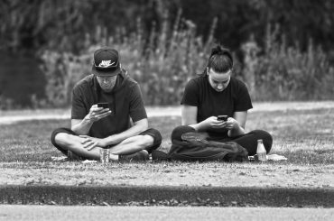 zwei junge Männer mit smartphone sitzen auf einer Wiese
